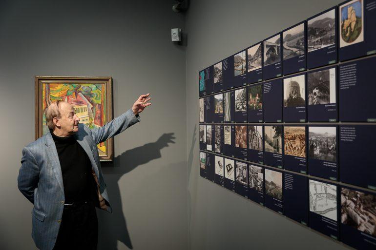 """Karl A. Kubinzky führt durch die Ausstellung """"Dein Graz!"""" im Museum für Geschichte. Er deutet mit der Hand auf die ausgestellten Werke."""