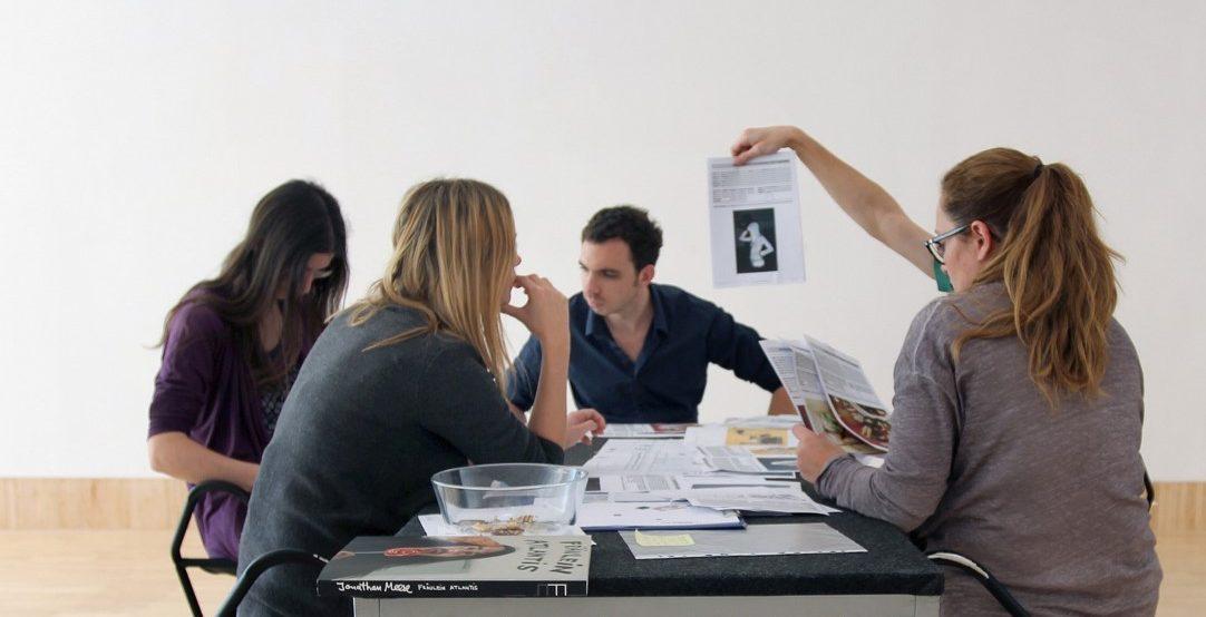 """Arbeitssituation im Vermittlungsprojekt """"Like it! Facebook friends kuratieren"""", Gruppe von jungen Menschen sitzen um einen Tisch mit Arbeitsblättern"""