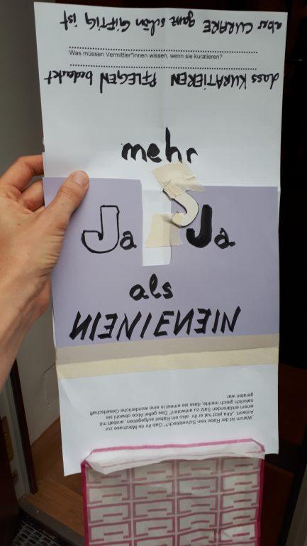 """Ein Produkt der interaktiven Workshopsequenz zu Utopien der Co-Produktion von Kurator*innen und Vermittler*innen, Hand hält Plakat mit der Aufschrift """"Mehr Ja Ja als Nein Nein"""""""