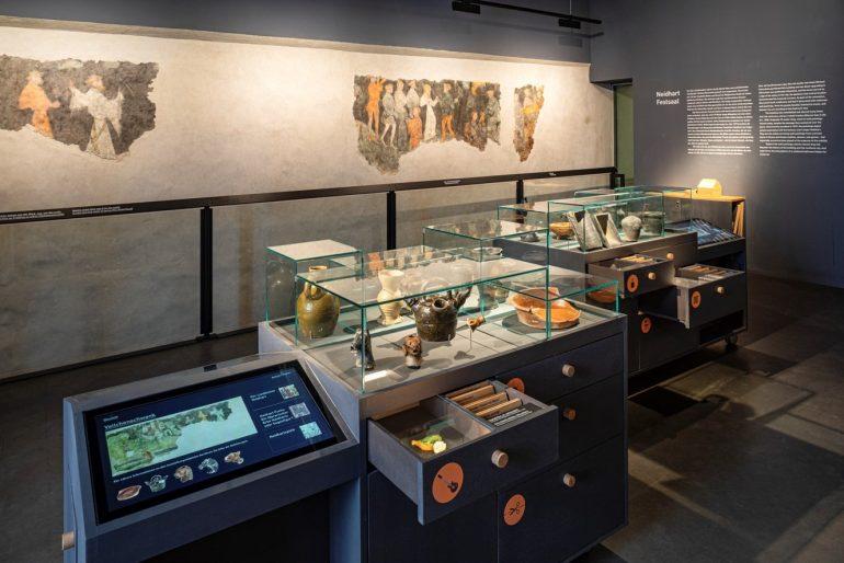 Innenansicht des neugestalteten Neidhardt-Festsaals mit Plakaten, Computer und Glasvitrinen