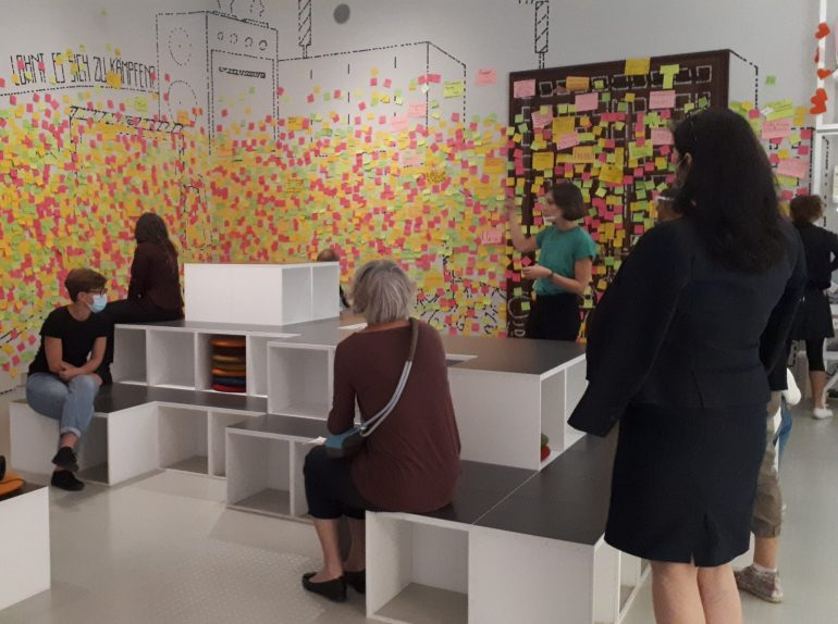 Workshop-Sequenz im hdgö mit Besucher*innen auf weißen Blöcken sitzend und bunten Post-Its auf den Wänden