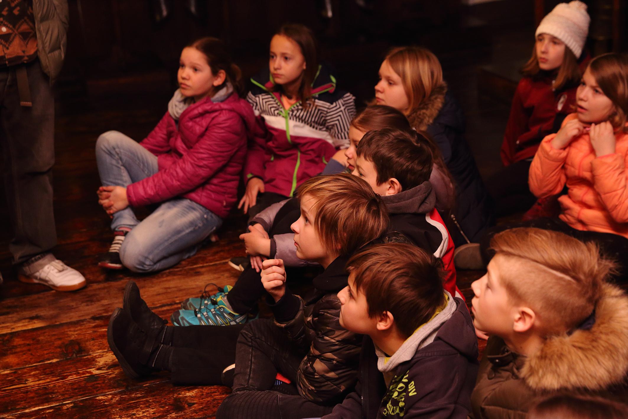 Schüler*innen sitzend im Museum