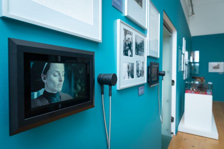 """Bilderrahmen mit Fotos und Lautsprecher auf einer blauen Wand in der Ausstellung """"Die Jagd ist weiblich"""" im Jagdmuseum Schloss Stainz."""