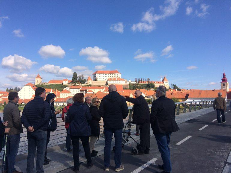 Gruppe von Menschen auf der Straße blickt auf eine von der Sohne bestrahlte Stadt.