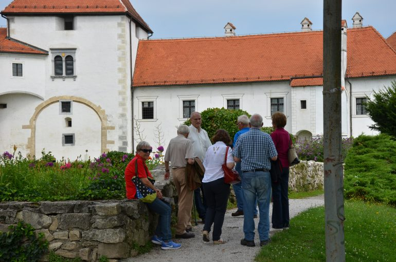 Leopold Toifl steht mit einer Gruppe von Menschen im Rahmen einer Führung vor einem Gebäude mit rotem Dach in Varzdin (Kroatien).