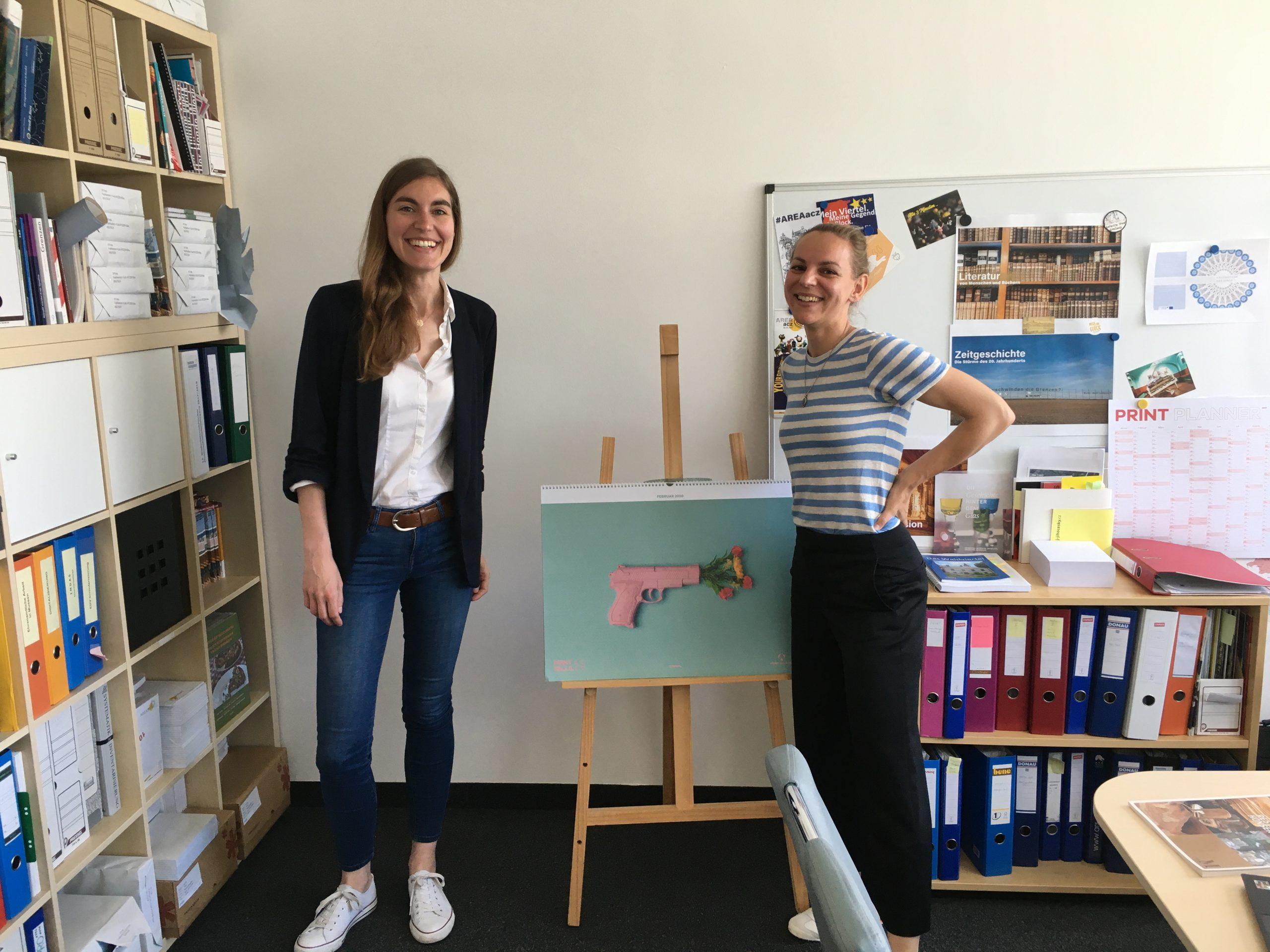 Christa Zahlbruckner (Sammlungsdigitalisierung) und Elisabeth Schlögl (Mitarbeiterin Museumsforum) stehen in einem Büro vor Ordnern und einer Staffelei.