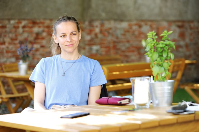 Elisabeth Schlögl mit blauem T-Shirt und Sonne im Gesicht beim Gespräch mit Rebecca Gahr im Gastgarten des Café Grün im Volkskundemuseum Graz
