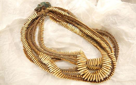 sechs Ketten mit Brüllaffen-Reißzähnen, Männerkunst für die Frauen ist bei den Asurini die schwere und eindrucksvolle Brüllaffen-Zahnkette von bis zu 1000 Reißzähnen des Brüllaffen. Die Mädchen mit Adlerflaumfedern im Haar als Gehilfinnen und Partnerinnen des Asurini-Schamanen im ekstatischen Tanz sind geschmückt mit schweren Brüllaffenzahnketten und den Armreifen mit eingelegten Knochenplättchen, Asurini vom Ipiacaba (1971), Foto: Universalmuseum Joanneum/J.J. Kucek